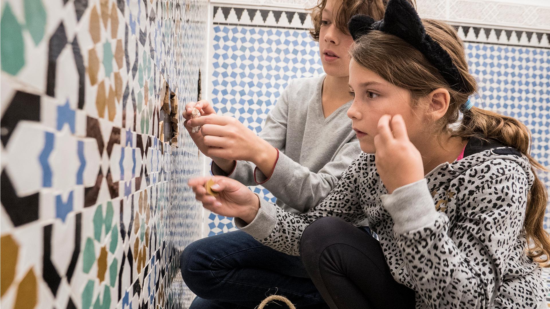 Kinderen in Tropenmuseum spelen met gesneden tegels bij ZieZo muur (tegels gesneden door Laser Chief)